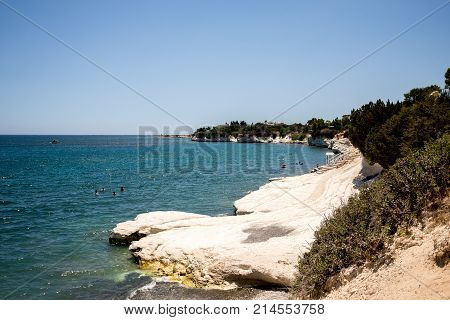 Scenic Governor's white limestone beach with tourists swimming between Larnaca and Limassol Cyprus