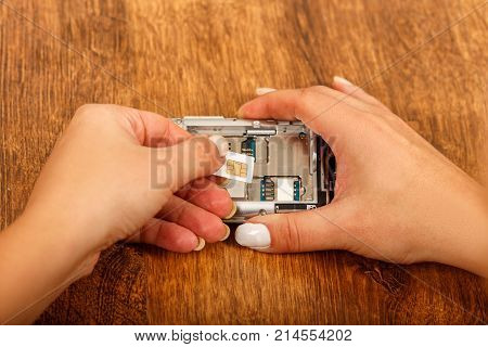 change of the SIM card in a smartphone on wooden table. female hands insert a SIM card in the phone