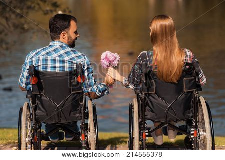 A couple of invalids on wheelchairs met in the park. A man and a woman are holding a bouquet of flowers. They are sitting on the shore of the lake.