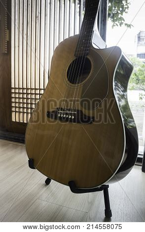 Acoustic guitar resting against mirror background stock photo