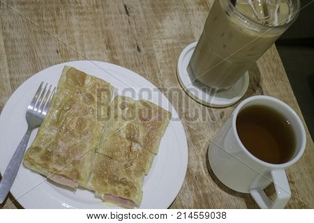 Breakfast set of coffee drink and fried ham cheese roti stock photo