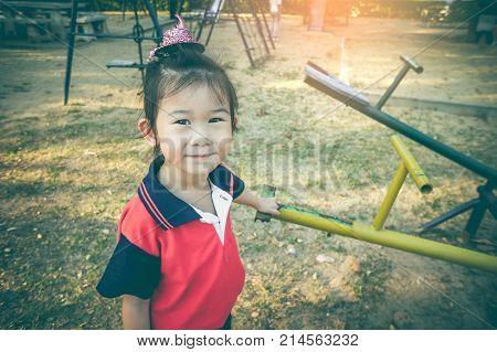 Asian Child Standing Near Seesaw At Children Playground. Vintage Tone.