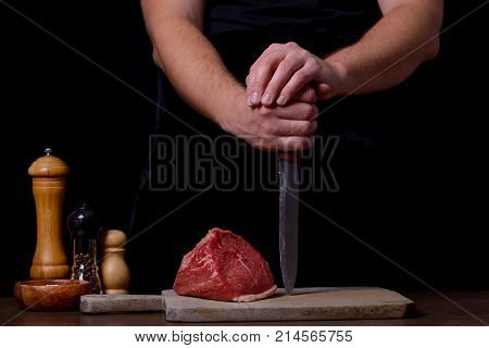 Butcher With Knife And Raw Steak And Spices