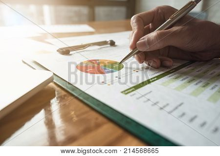 Close Up Shot Of A Man's Hand Holding A Ball Point Pen On The Financial Document, Business Concept