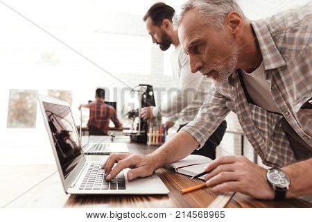Three men set up a self-made 3d printer to print the form. They check the scribes of the 3d printer on the laptop. An elderly man directs the process of starting and printing a printer.