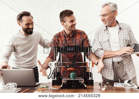 Three men are working on preparing a 3d printer for printing. Two men set up a 3d printer, an elderly man holds a laptop in his hands and watches the process.