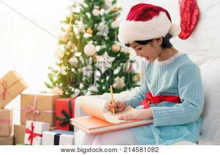 Cute little Asian child girl writes the letter to Santa Claus near Christmas tree indoors at home. Merry Christmas and Happy Holidays!