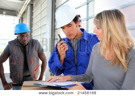 Manager with store men controlling goods delivery