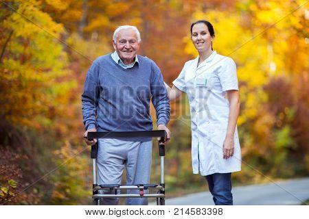 Nurse helping elderly senior man. Senior man using a walker with caregiver outdoor