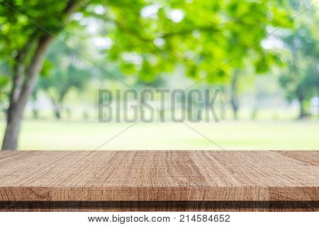 Empty wood table over blur green park nature background tabletop shelf counter for product display montage