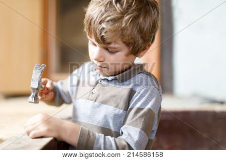 happy little kid boy helping with toy tools on construction site. Funny child of 7 years having fun on building new family home. Kid with nails and hammer helping father to renovate old house