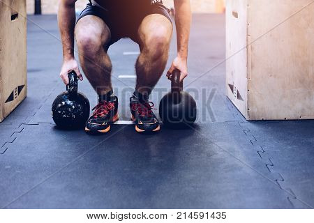 Man Pulling Kettlebells Weights In The Functional Fitness Gym