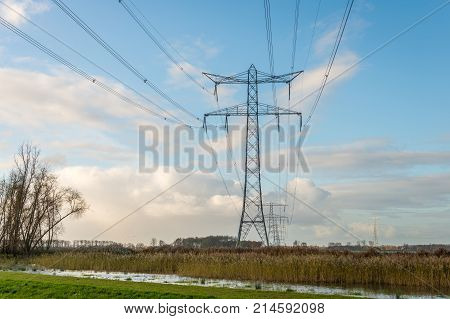 High-voltage lines and pylons in a Dutch polder landscape. In the background small high voltage pylons of another route are just visible. It is a cloudy day in the fall season.
