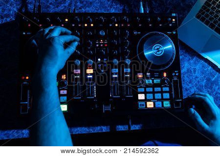 hands of DJ and professional music equipment mixer controlling buttons and levels music the view from the top