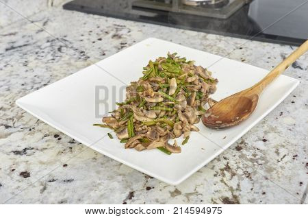 Vegan food in a white dish mushrooms and asparagus.
