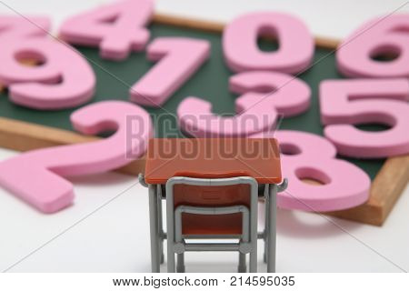 Numbers, desk and blackboard on white background. Educational concept of mathematics and arithmetic.