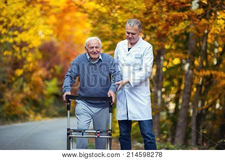 Male nurse assisting senior patient with walker outdoor