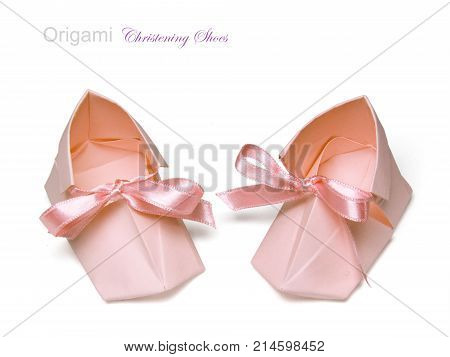 Paper baby girl christening shoes on a white background
