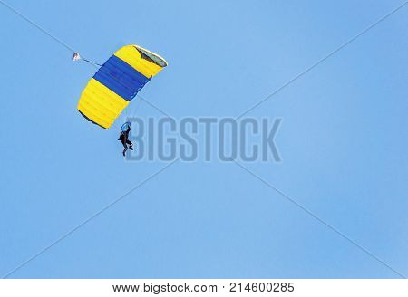 Paratrooper with an open parachute against a blue sky. Concept of freedom and flying with a free space for your text.