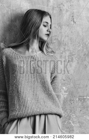 Pretty girl or cute young woman with blond hair and adorable face in blue sweater and fashionable grey culottes pants on textured wall background