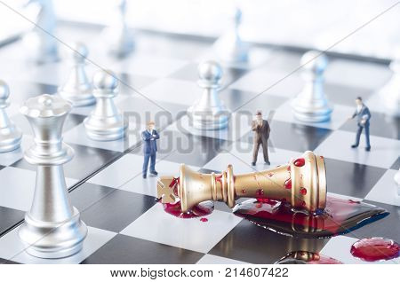 A conceptual photo with chess pieces, toy businessmen and blood on a chessboard. Business, law or political concept, which could represent war of corporations, geopolitical situation and so on. Selective focus.