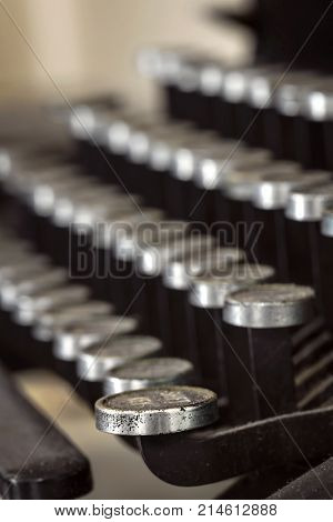 Vintage typewriter keys covered in dust.  Selective focus on front key.