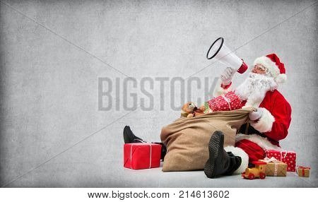 Santa Claus with a bag full of presents talking with megaphone