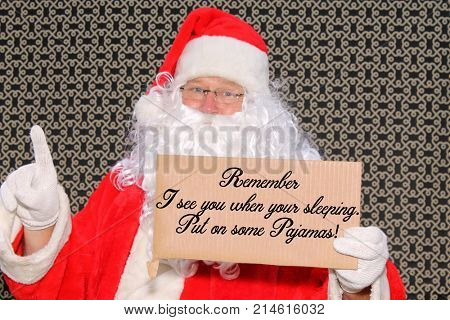 Santa Claus with a funny Cardboard Sign Santa Sign reads REMEMBER I SEE YOU WHEN YOUR SLEEPING, PUT ON SOME PAJAMAS!