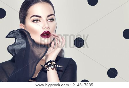 Beauty Fashion model girl with dark lips portrait, wearing stylish chiffon dress. Sexy woman portrait with perfect makeup and manicure, trendy accessories and fashion wear. Beauty trends. On gray.
