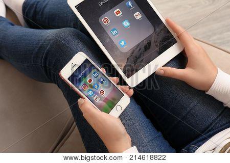 KIEV, UKRAINE - OCTOBER 03, 2017: Woman holding iPhone SE displaying social media icons and iPad mini 4 on knees