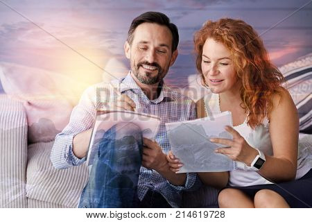 Brainstorm. Friendly enthusiastic cheerful people sitting together in a comfortable room and smiling while holding notebooks and working at their common project