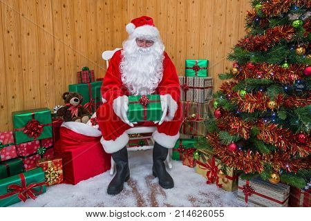 Santa Claus in his grotto surrounded by a Christmas tree with presents and gift wrapped boxes
