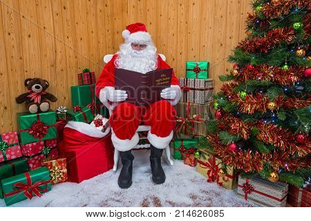 Santa Claus sitting in his grotto surrounded by a tree with presents and gift wrapped boxes whilst he reads his favourite book - The night before Christmas