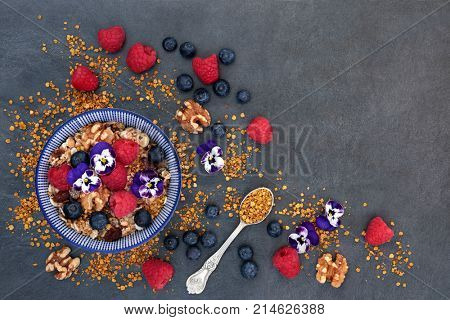 Breakfast health food concept with granola, pollen grain, fresh berry fruit, nuts and edible flowers High in antioxidants, anthocyanins, protein and vitamins . Top view.