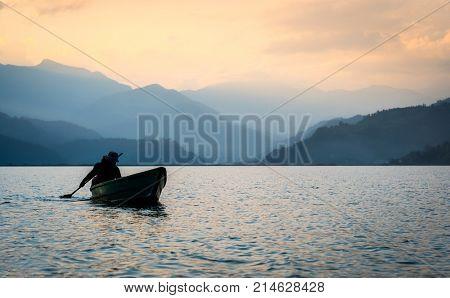 Lonely fisherman on the boat fishing in Phewa lake, Nepal