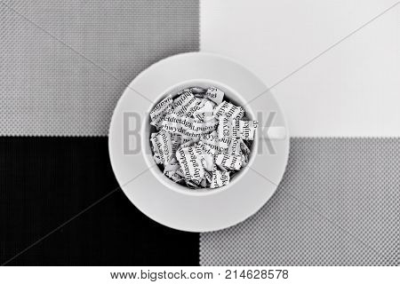 a printed letter or document broken into a thousand pieces in a white ceramic coffee cup placed on a black, gray and white background