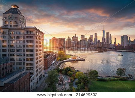 Famous Brooklyn Bridge in New York City with financial district - downtown Manhattan in background. Sightseeing boat on the East River and beautiful sunset over Jane's Carousel. poster