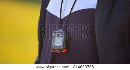 Coach with a stopwatch and blue tracksuit. Yellow background with space.