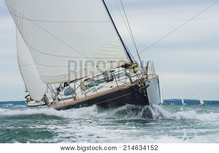 Two sailing boats, sail boats or yachts racing at sea