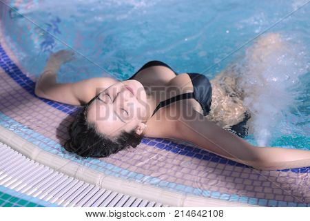 Young woman enjoying jacuzzi in a spa center. Young woman. jacuzzi