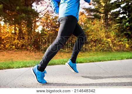Unrecognizable young athlete in blue jacket running outside in colorful sunny autumn nature. Trail runner training for cross country running.