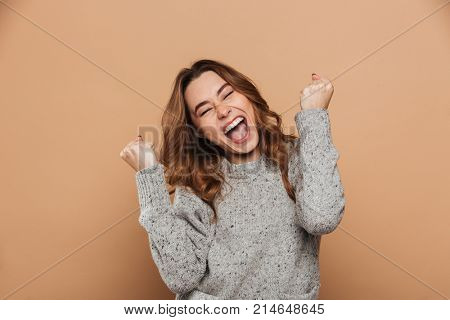 Close-up portrait of happy screaming woman with closed eyes showing winner gesture, isolated over beige background