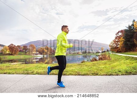 Young athlete in yellow jacket running outside by the lake. Trail runner training for cross country running in colorful sunny autumn nature.
