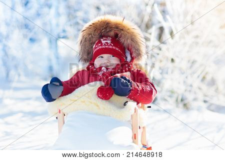 Sled And Snow Fun For Kids. Baby Sledding In Winter Park.