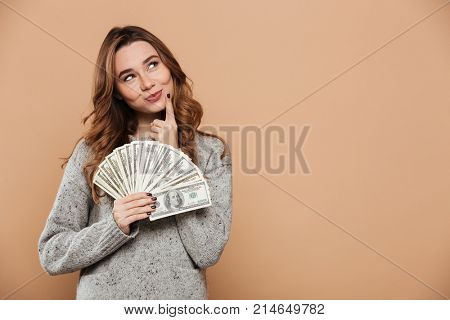 Close-up portrait of playful beautiful woman in gray woolen sweater holding bumch of money, looking aside, isolated over beige background