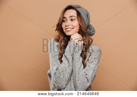 Charming young brunette woman in warm clothes holding hands, looking aside, isolated on beige background