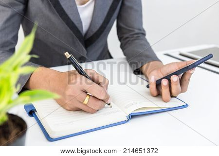 Finance managers task use smart phone and note or check for about finance cost at office Businessman recheck new plan financial graph data. Business and strategy investment concept.