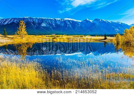 Rocky Mountains are reflected in the smooth water of Lake Abraham. Indian Summer in the Rockies. Concept of ecological and active tourism