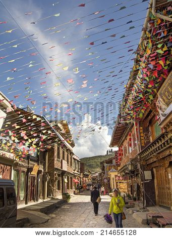 SHANGRI LA CHINA JUNE 24 2015: Prayer flag decorate in old town. People are walking through the historical old town in chinese city shangri-la alias zhongdian Yunnan China.