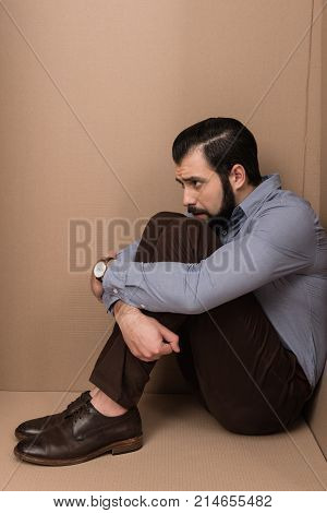 depressed man sitting in big cardboard box